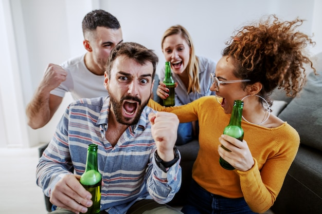 Groep vrienden zitten in de woonkamer en juichen voor hun favoriete voetbalteam. ze houden allemaal bierflesjes.