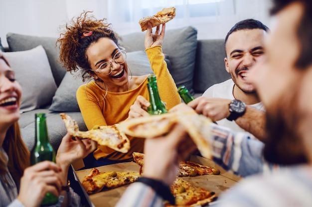 Groep vrienden zittend op de vloer in de woonkamer, bier drinken en pizza eten.