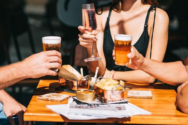 Groep vrienden zittend op een zomerterras met bier en wijn in hun handen en snacks op tafel
