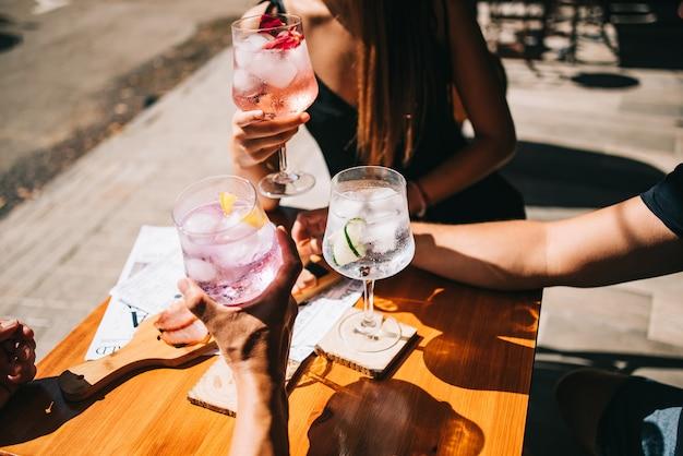 Groep vrienden zittend op het zomerterras met cocktails en snacks op tafel