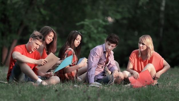 Groep vriendenstudenten die op het gras in het park zitten Premium Foto