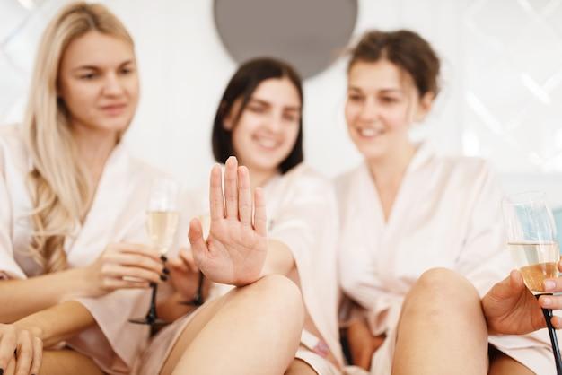 Groep vriendinnen met champagne ontspannen op pedicure procedure in de schoonheidssalon.