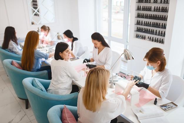 Groep vriendinnen ontspannen op manicure procedure in de schoonheidssalon.