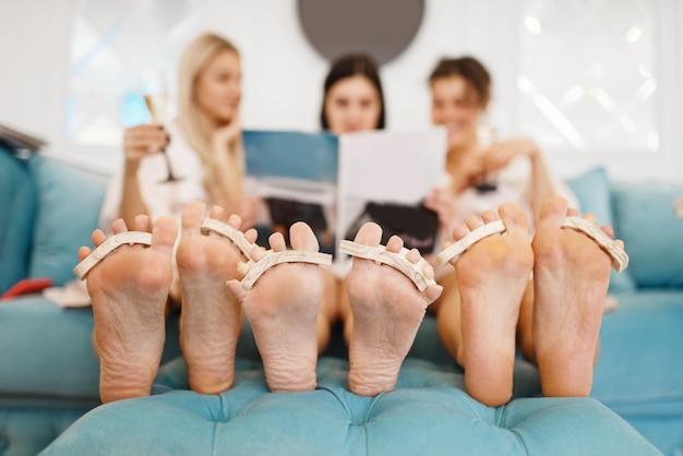 Groep vriendinnen ontspannen op pedicure procedure in de schoonheidssalon.