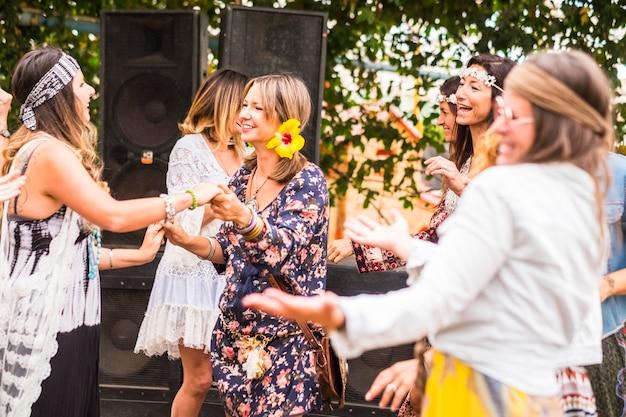 Groep vrije en hippie rebelse jonge vrouwen in alternatieve stijl die samen dansen en vieren met vreugde en geluk op een natuurlijke plek binnen en buiten. mooie levensstijl voor mooie mensen