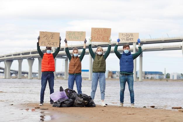 Groep vrijwilligers die borden opheffen die bij de vuilniszakken bij de kustlijn staan