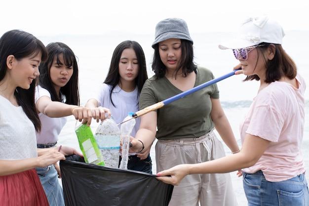 Groep vrijwilligers die overzees strand schoonmaken