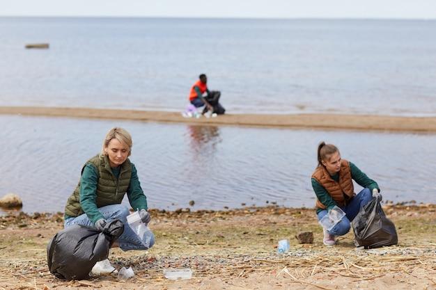 Groep vrijwilligers die samen de oever van de rivier schoonmaken, zijn ze in ecologische organisatie