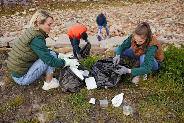 Groep vrijwilligers ruimen het afval op in zakken die ze beschermen en de natuur redden