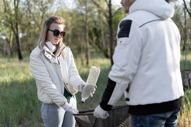Groep vrijwilligers ruimt de vuilnis op in het park. drie mensen helpen het gebied vrij te maken