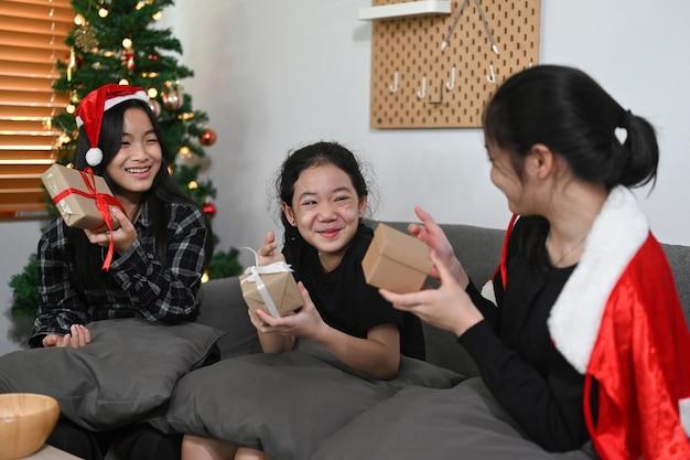 Groep vrolijke aziatische meisjes die kerstmis thuis vieren.