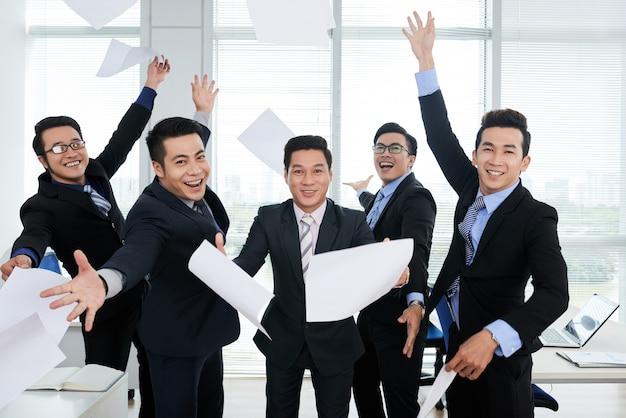 Groep vrolijke aziatische zakenlieden die in kostuums documenten in lucht in bureau overgeven