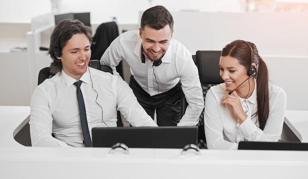 Groep vrolijke collega's die in callcenter werken