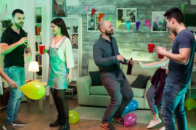 Groep vrolijke jonge mensen dansen op feest met goede muziek en ballonnen.