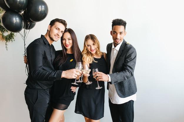 Groep vrolijke jonge mensen in trendy kleding die glazen met champagne opheft
