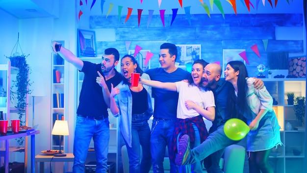 Groep vrolijke jonge mensen op een feestje in een appartement met neonlicht dat een selfie maakt.