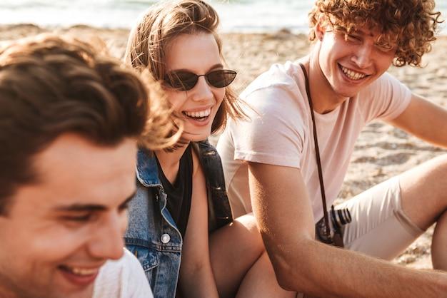Groep vrolijke jonge vrienden die leuke tijd hebben samen op het strand