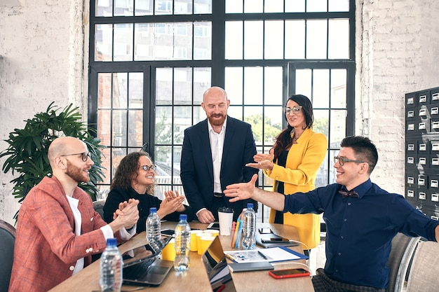 Groep vrolijke lachende gelukkige mensen vieren overwinning met armen omhoog mediation aanbieding high five vriendschap deal prestatie staking koopje goed nieuws vriendelijke toestemming succesvolle effectieve strategie