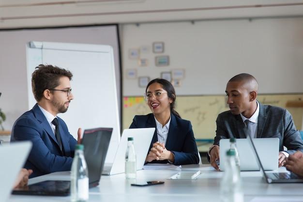Groep vrolijke managers die tijdens vergadering communiceren