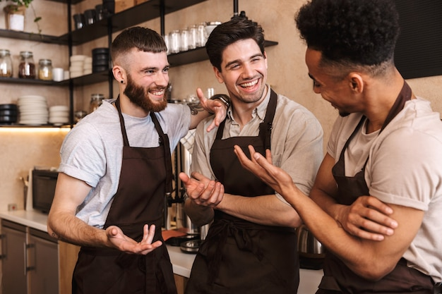 Groep vrolijke mannenbarista's die schorten dragen die aan de balie in café binnenshuis werken, pratend