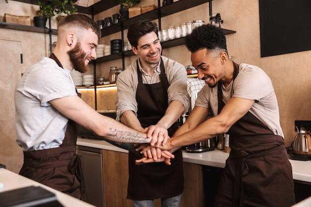 Groep vrolijke mannenbarista's die schorten dragen die aan de balie in café binnenshuis werken