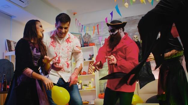 Groep vrolijke mensen verkleed voor halloween dansen op een wild feest.