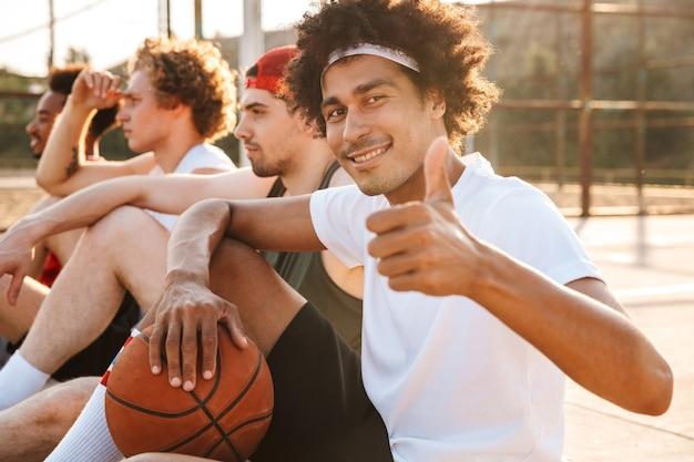 Groep vrolijke multi-etnische vrienden basketbalspelers