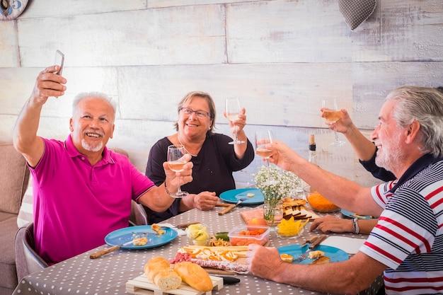 Groep vrolijke oude senioren thuis tijdens de lunch nemen selfie foto en klinken met witte wijn om vriendschap te vieren en te genieten
