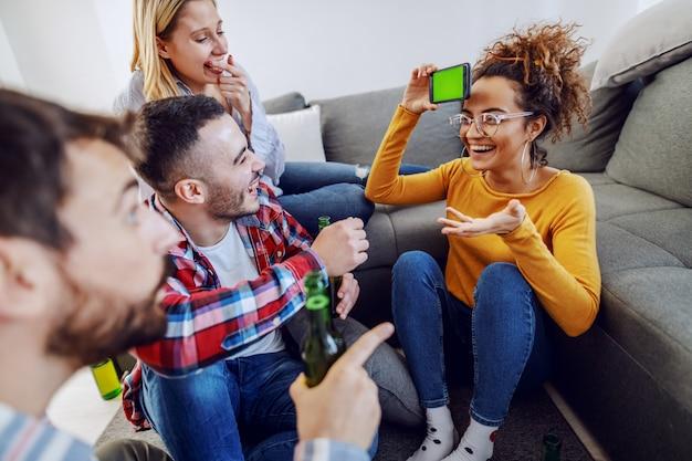 Groep vrolijke speelse vrienden die charades met slimme telefoon spelen. interieur.