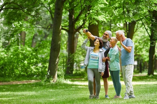 Groep vrolijke sportieve senior volwassen mannen en vrouwen staan samen in park nemen groep selfie geschoten op slimme telefooncamera