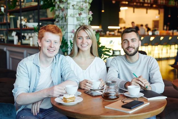 Groep vrolijke studenten van de universiteit die na de lessen in café ontspannen, thee hebben en genieten van het samenzijn