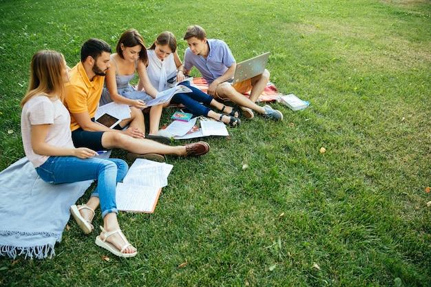 Groep vrolijke studententieners in toevallige uitrustingen met notaboeken en laptop