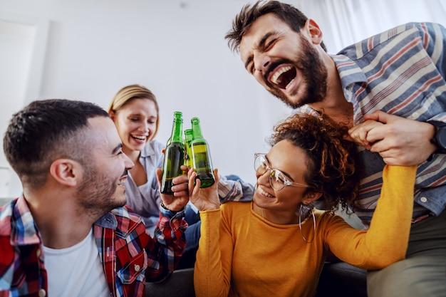 Groep vrolijke vrienden die pret hebben thuis, met bier roosteren en lachen.