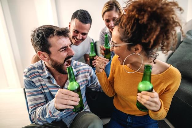 Groep vrolijke vrienden die thuis en voetbalwedstrijd op televisie letten zitten. hun favoriete team wint.