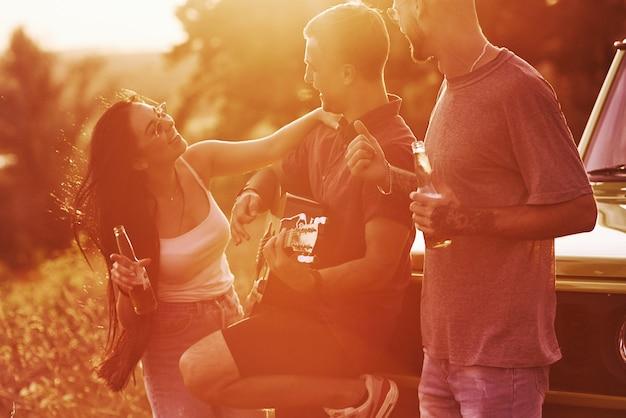 Groep vrolijke vrienden hebben een leuk weekend op een zonnige dag in de buurt van hun groene auto buitenshuis
