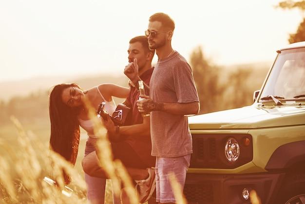 Groep vrolijke vrienden hebben een leuk weekend op een zonnige dag in de buurt van hun groene auto buitenshuis Premium Foto