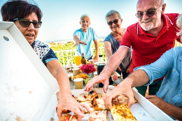 Groep vrolijke vrienden hebben samen plezier in vriendschap die pizza eten en eten thuis of in een openluchtfeestrestaurant