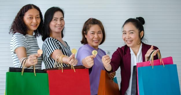 Groep vrouw met cryptogeld munten en boodschappentassen bij de hand. concept van cryptocurrency