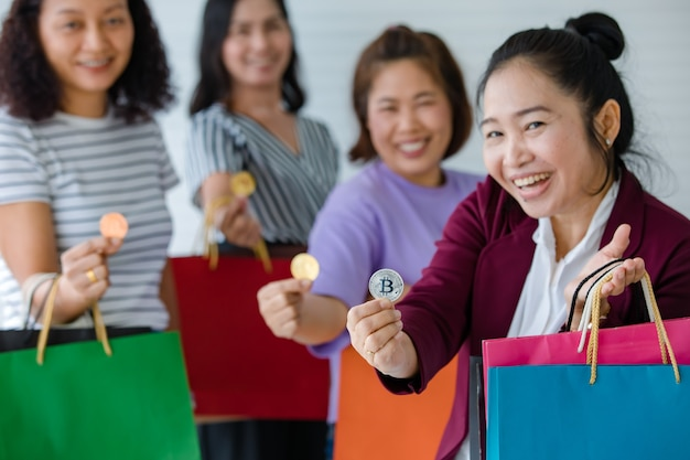 Groep vrouw met cryptogeldmunten en een verscheidenheid aan kleuren boodschappentassen bij de hand. concept van cryptocurrency-betaling en digitaal geld dat in het echte leven van moderne mensen wordt gebruikt.