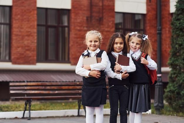 Groep vrouwelijke kinderen in schooluniform dat buiten samen is in de buurt van het onderwijsgebouw.
