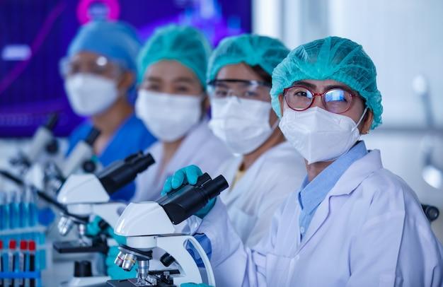 Groep vrouwelijke onderzoekers of wetenschappers die beschermende hygiënemaskers en medische uniformen dragen die bij elkaar zitten en werken met microscopen en reageerbuis in het laboratorium en naar de camera kijken.