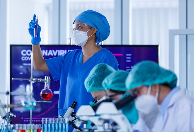 Groep vrouwelijke onderzoekers of wetenschappers die beschermende hygiënemaskers en medische uniformen dragen die met microscopen en reageerbuis in laboratorium werken die over coronavirussituatie bestuderen en analyseren.