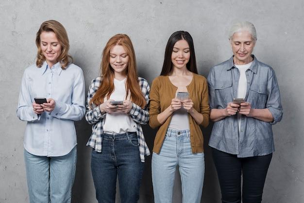 Groep vrouwelijke vrienden die op telefoons texting