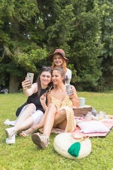Groep vrouwelijke vrienden die selfie op cellphone nemen die in de picknick genieten van