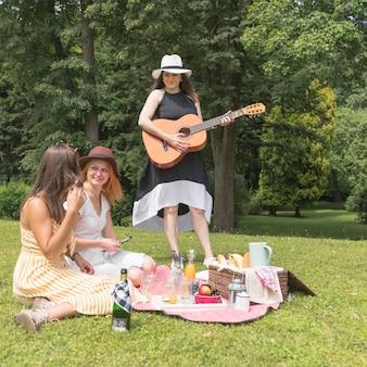 Groep vrouwelijke vrienden die van muziek en voedsel in de picknick genieten
