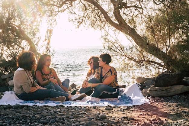 Groep vrouwelijke vrienden gaan samen zitten op het stenen strand en genieten van vriendschap, glimlachen en spreken