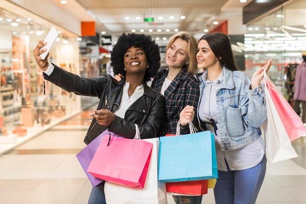 Groep vrouwen die een selfie na het winkelen nemen