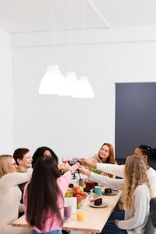 Groep vrouwen die een toost met exemplaarruimte maken