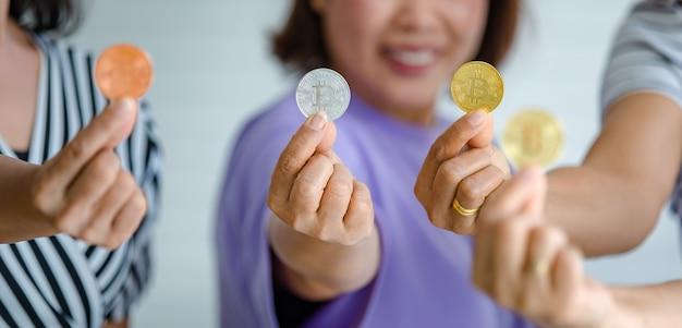 Groep vrouwen die een verscheidenheid aan kleuren bitcoin vasthouden en aan de camera laten zien. cryptocurrency en geld bedrijfsconcept.