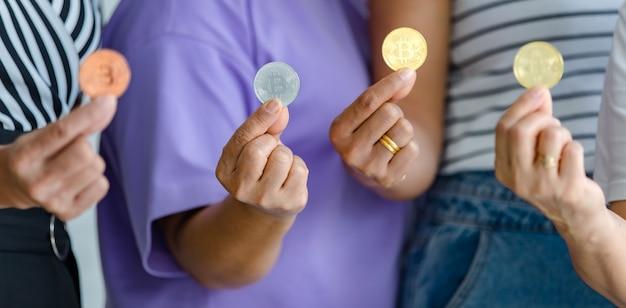 Groep vrouwen die een verscheidenheid aan kleuren bitcoin vasthouden en aan de camera laten zien. cryptovaluta en geld